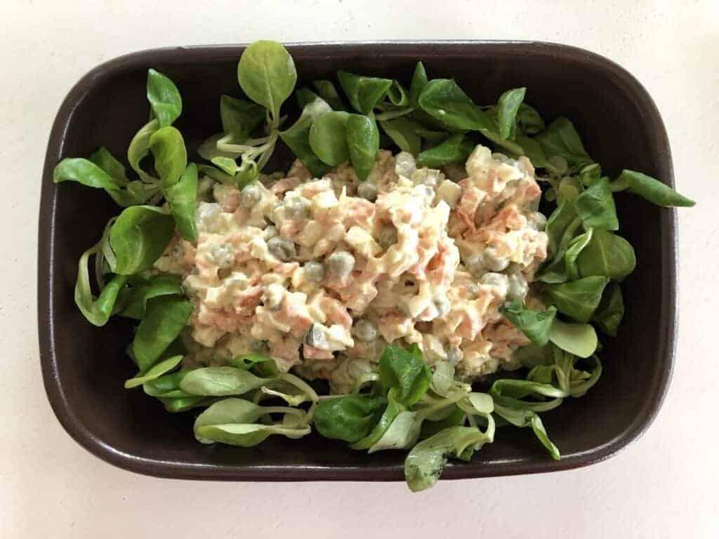 Polish vegetable salad in a black bowl.