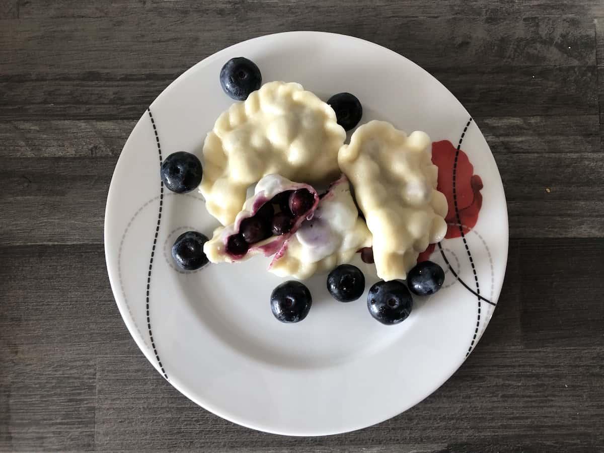 blueberry pierogi in a white plate.