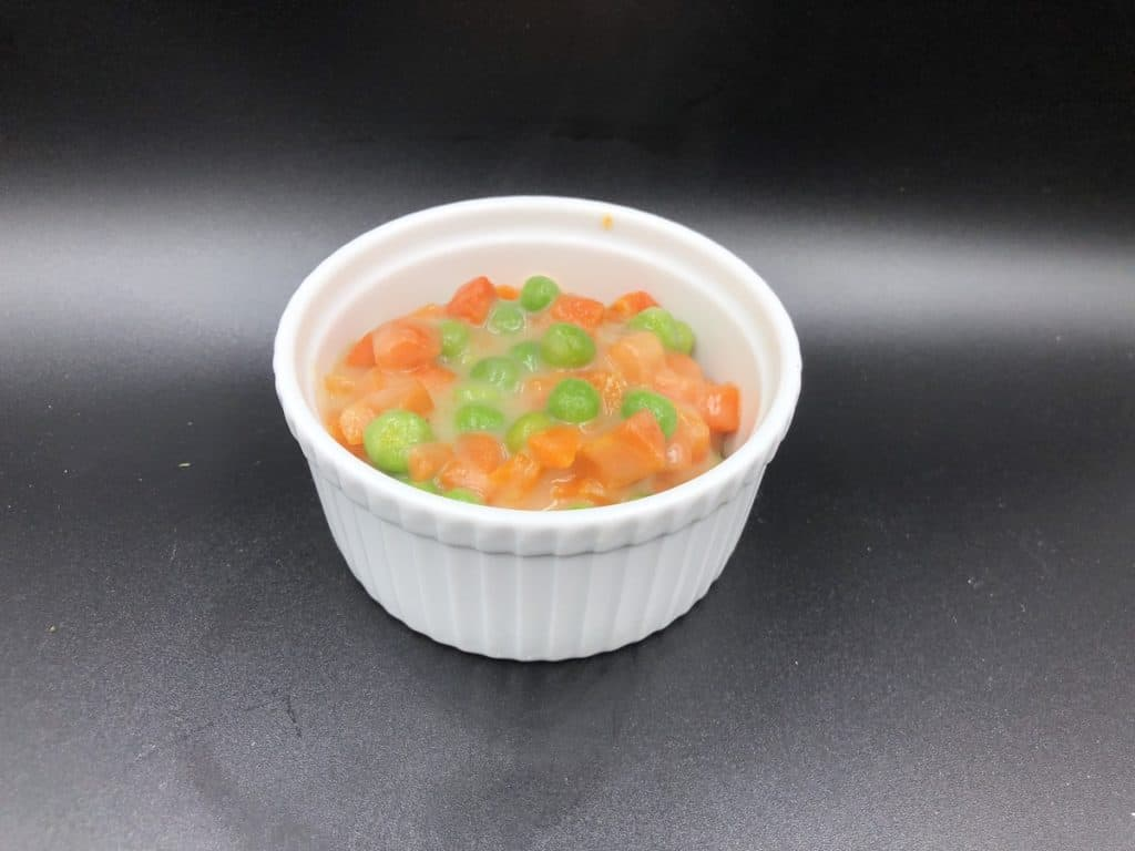 Creamed peas and carrots in a white bowl.