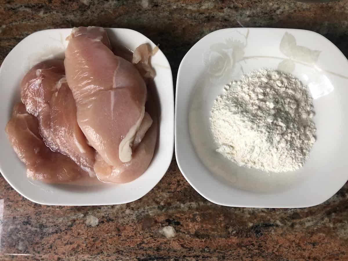 Uncooked chicken breasts and flour in a white plate.
