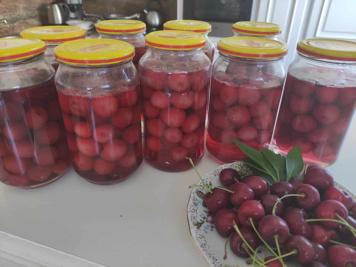 Add cherries to glass jars with water.