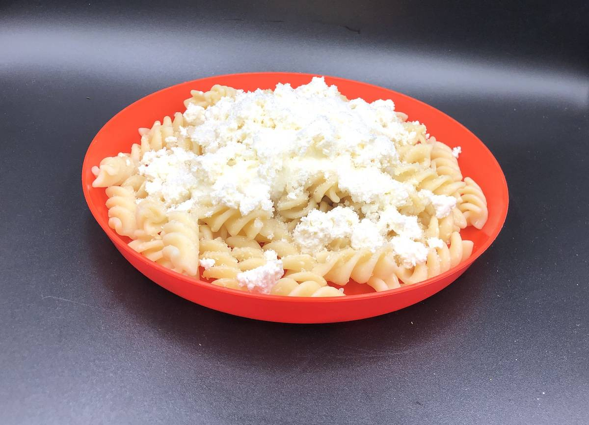 Polish noodles and cottage cheese in an orange bowl.