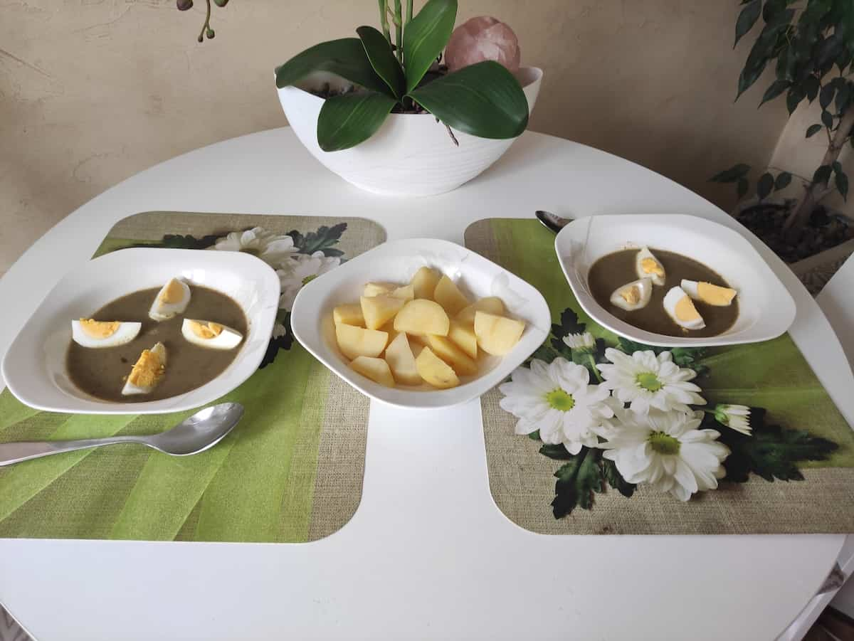 Bowls of sorrel soup with boiled eggs on top and boiled potatoes in another bowl.