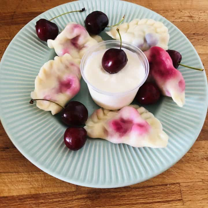 Top view of a blue plate with cherry pierogi.